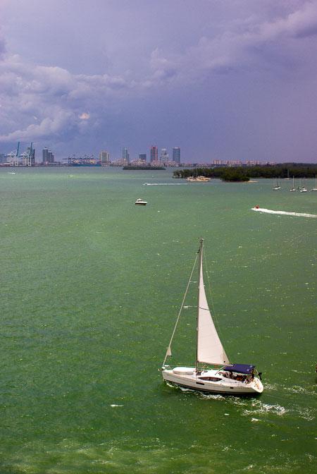 sailboat entering harbor ahead of storm