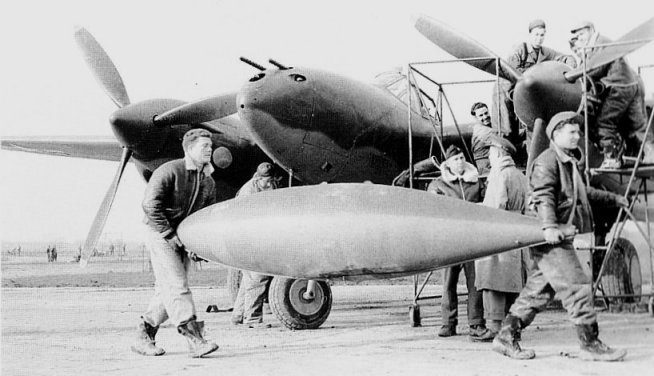 The 165 Gallon Lockheed Drop Tank in Front of a P-38 Lightning Fighter dated Nov 1943